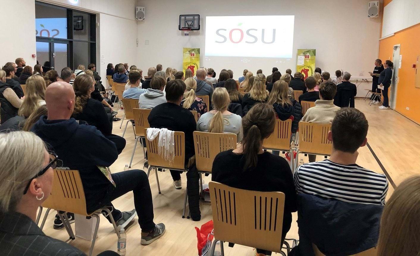 En sal fuld af mennesker der sidder og kigger op på en skærm hvor der står SOSU.