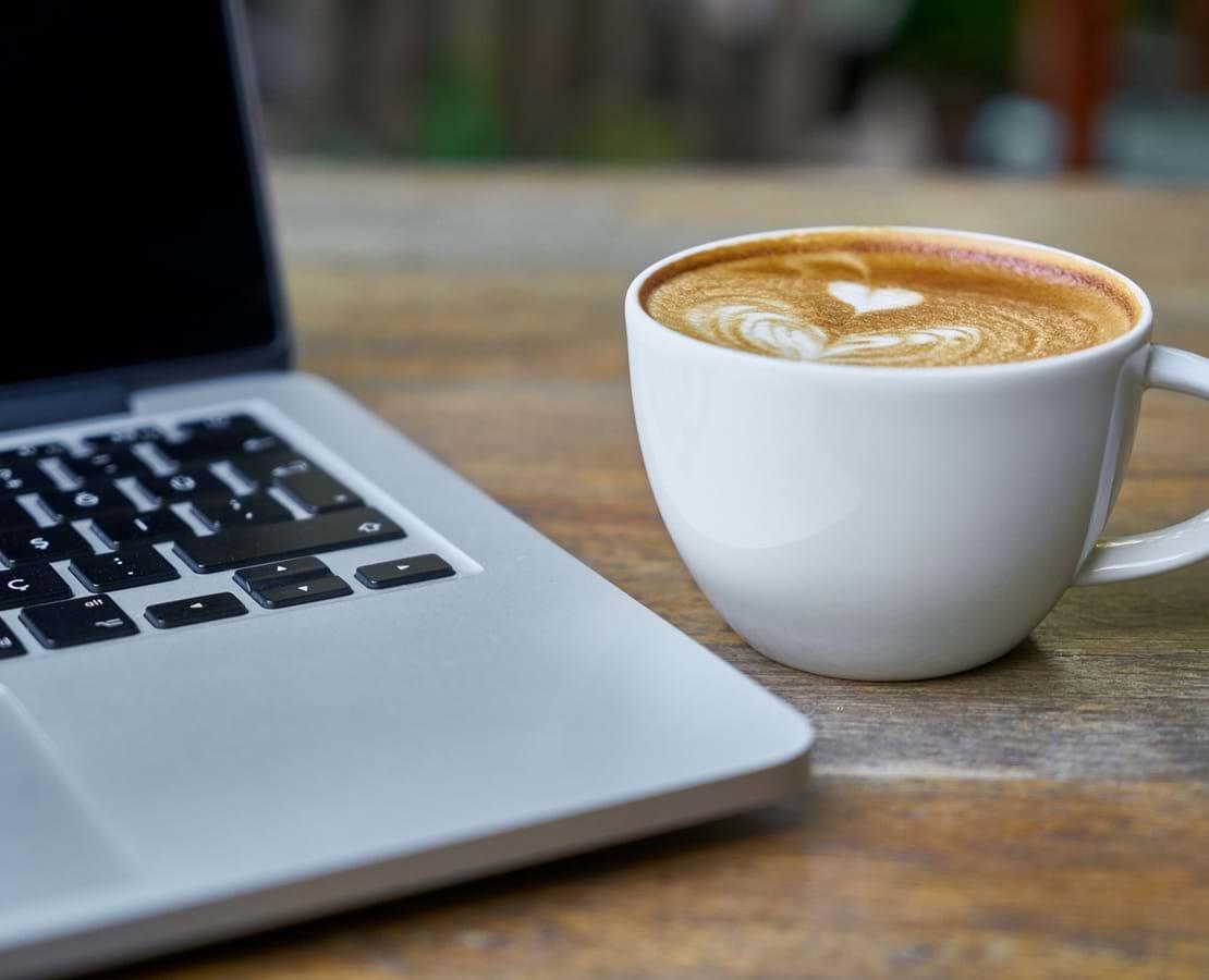 En kop cappucino med hjerte i mælkeskummet og en laptop ved siden af.