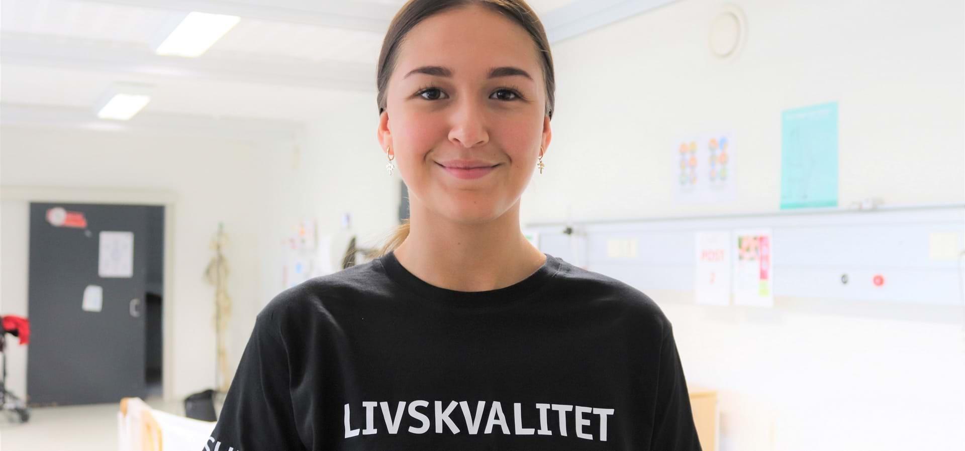 """Ung, kvindelig elev med """"Livskvalitet"""" skrevet på sind T-shirt smiler ind i kameraet."""