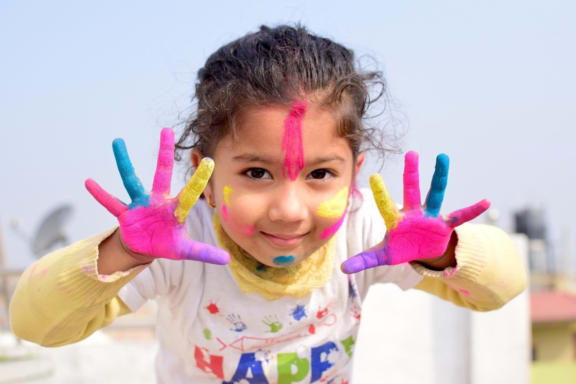 En lille pige kigger glad ind i kameraet. Hun har farverig maling på hænderne og i ansigtet.
