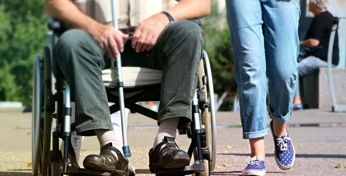 En mand i kørestol og en gående kvinde går tur sammen