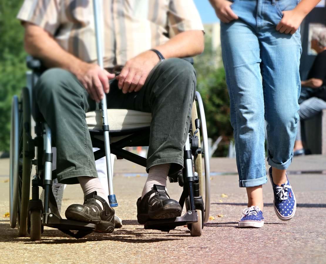 Social- og sundhedshjælper går tur sammen med en ældre mand i kørestol