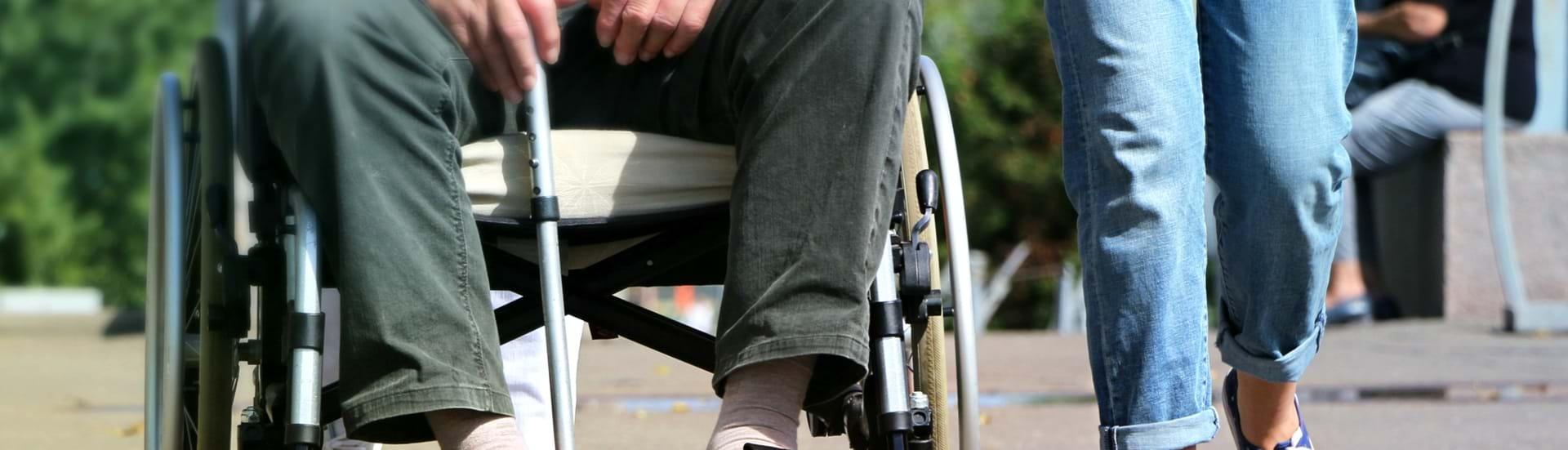 Social- og sundhedshjælper der går tur sammen med en ældre mand i kørestol