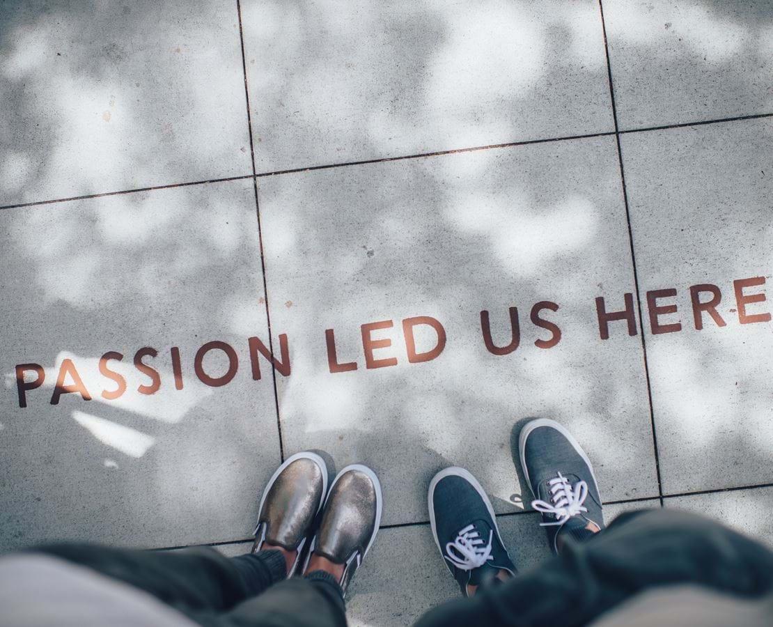 To personers fødder vises foran teksten 'Passion led us here' skrevet på fliserne de står på.
