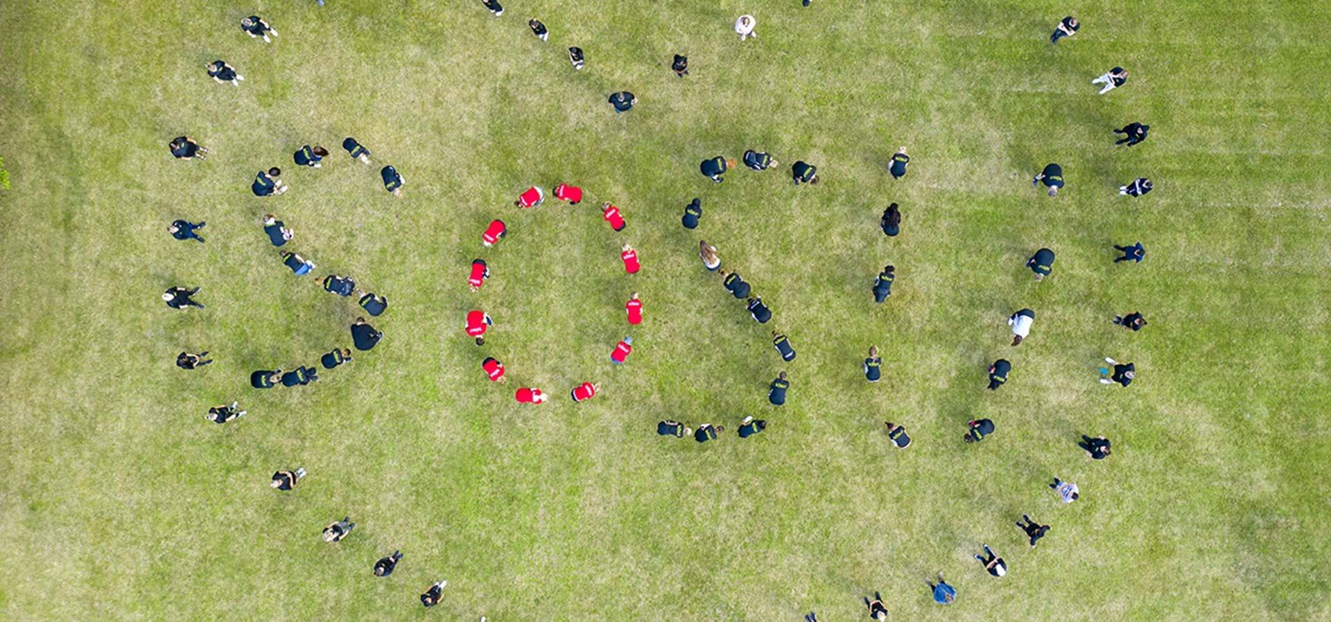 Elever er fotograferet fra oven med drone og danner med deres kroppe SOSU og et hjerte omkring.